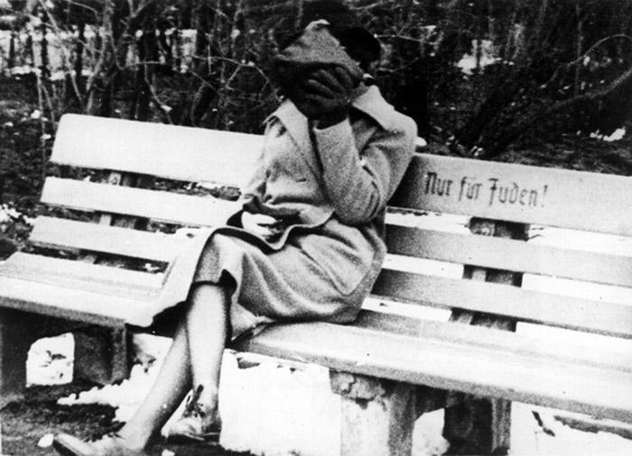 A Jewish woman hides her face as she sits on a Jew only bench.Germany 1938