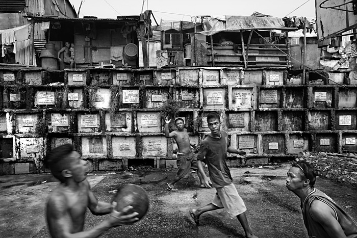 Boys playing basketball among the tombs of the Navotas Cementery.   Manila, Philippines