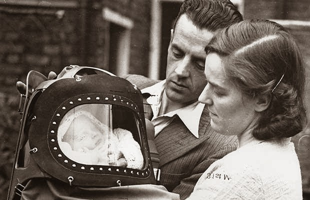 02 Neville Mooney, the first baby born in Britain as the country went to war, in his gas mask with his parents