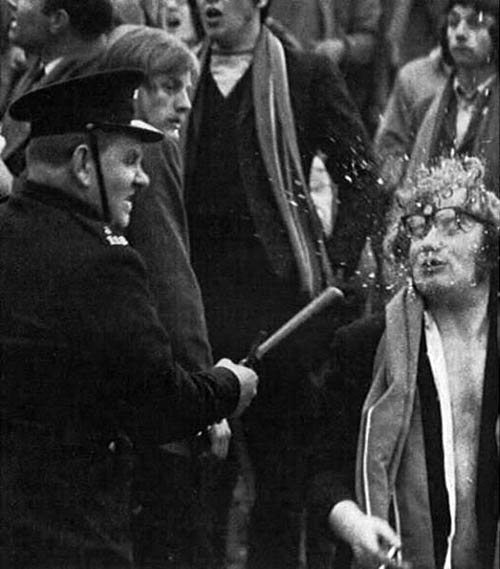 Gardaí officer smashes glasses off someones face as the police charge crowds after a game between Cork Hibernians and Linfield from Belfast.