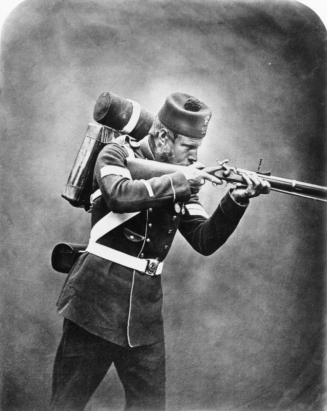 Portrait of Corporal James Tinn, 95th Regiment, wearing pack and aiming his rifle.