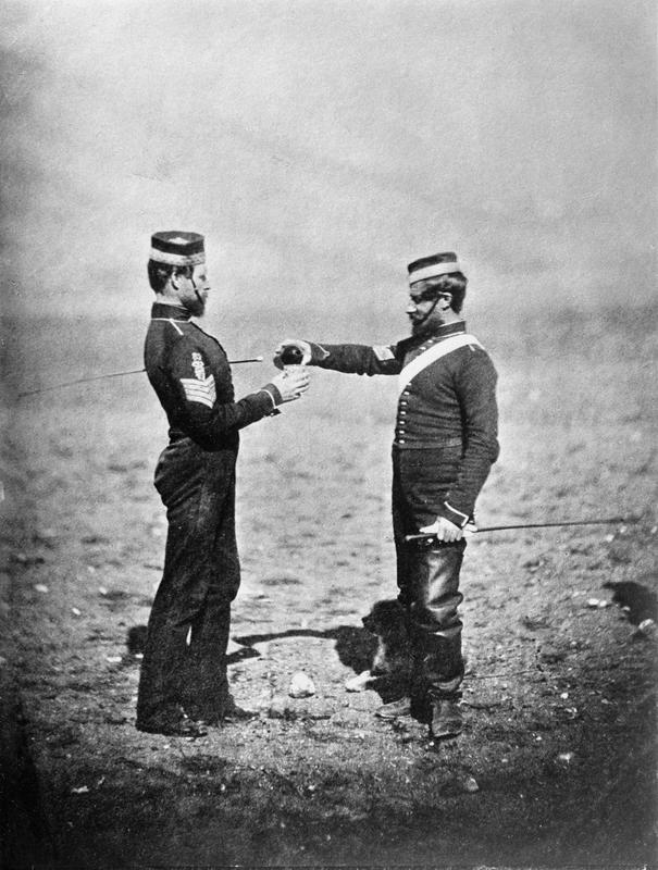 A sergeant of the 8th Hussars pours another a drink