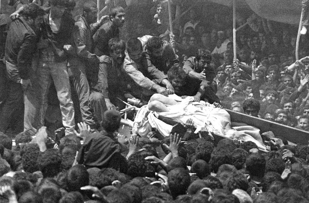 Ayatollah Khomeini's body falls from his coffin during his funeral, as frenzied mourners try to tear pieces from the shroud covering him, Teheran, 1989