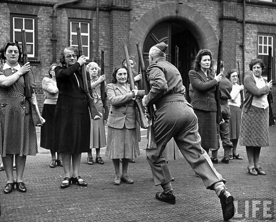 A sergeant drilling civilian members of the Women's Home Defence Corps, in the use of rifles during the Battle of Britain in 1940