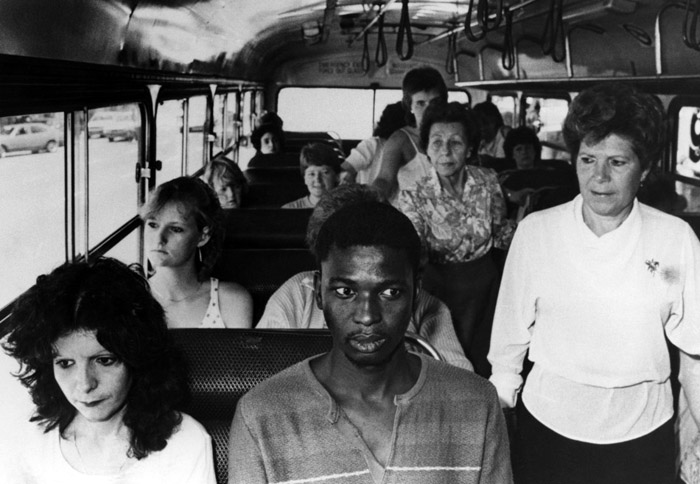 A young black man, in an act of resistance to South Africa's apartheid policies, riding a bus restricted to whites only, in Durban, South Africa, 1986
