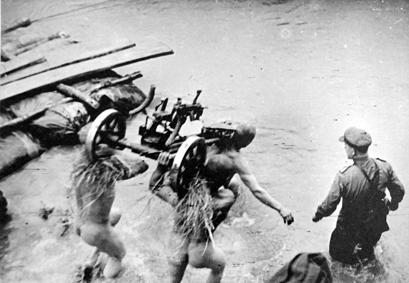 Naked Red Army soldiers carrying a DShK heavy machine gun across a river on 18 July, 1944.