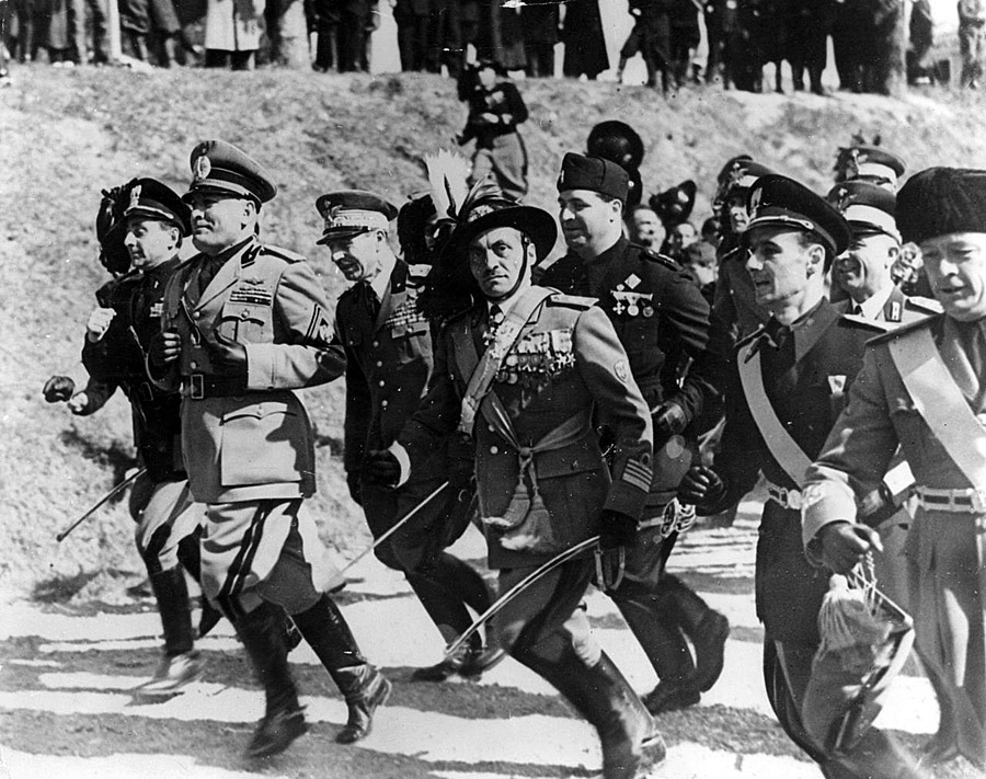Benito Mussolini runs with his officers in full military regalia, 1938