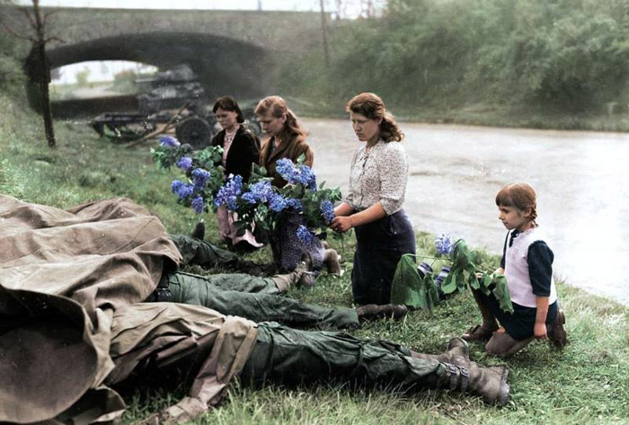 Russian women and children recently liberated from a Nazi concentration camp lay flowers at the bodies of four dead American soldiers. Hilden, Germany. 1945