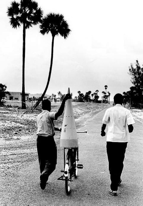 An Indian Space Research Organization scientist transporting a nose cone of a rocket on a cycle, 1968