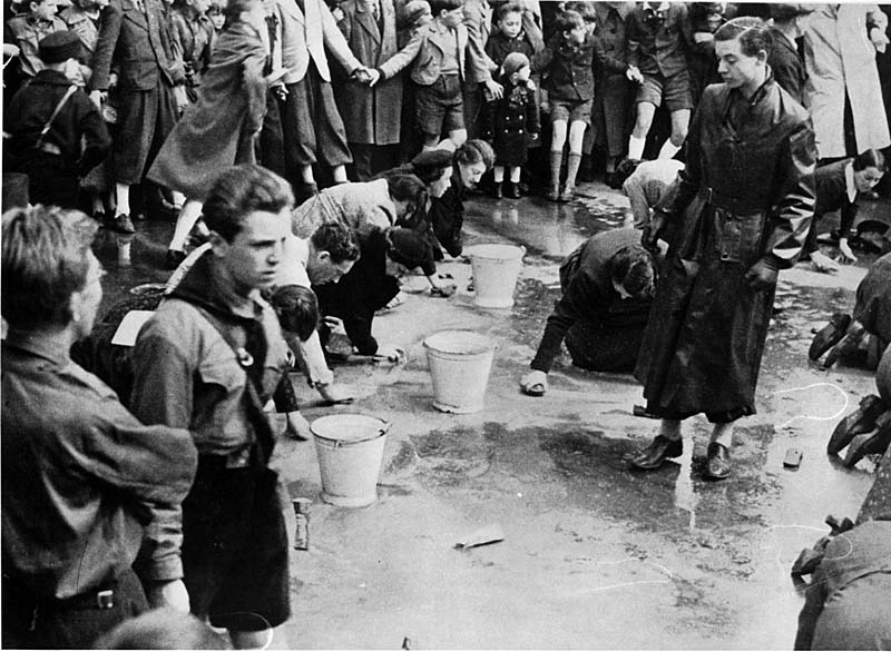 Hitler Youth forcing Jews to clean a street