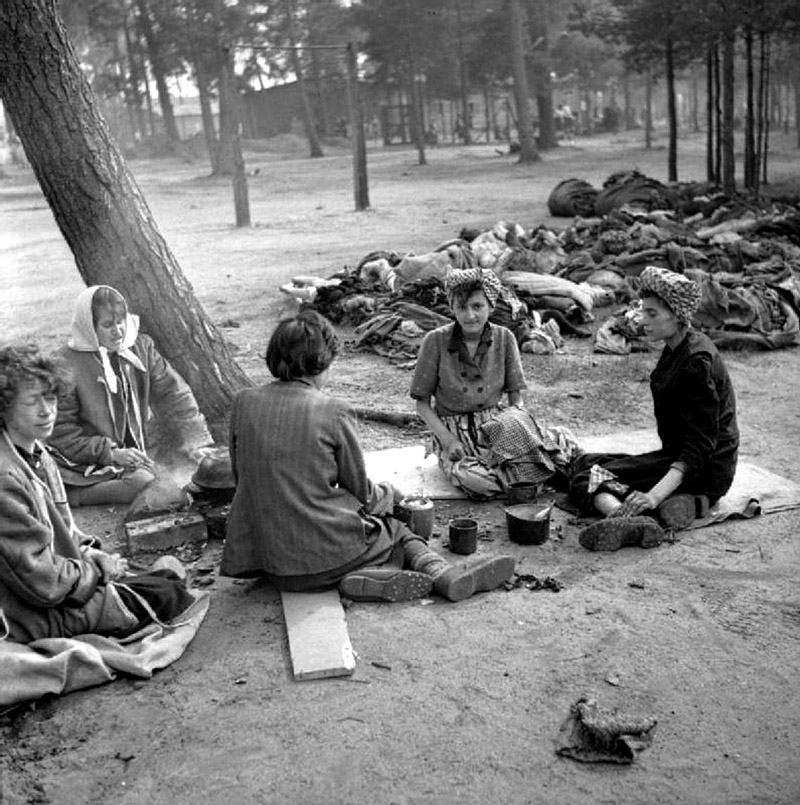 Newly liberated inmates of the Bergen-Belsen concentration camp prepare a meal outdoors near the heaped bodies of the dead, Germany, 18 April 1945