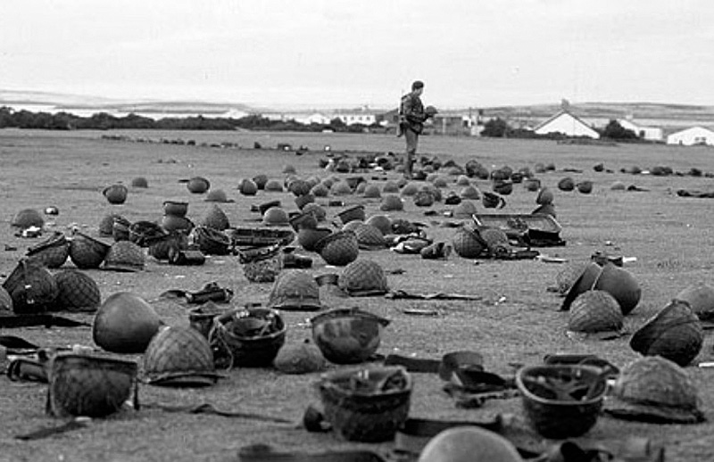 A British soldier surrounded by abandoned Argentinian helmets after the battle of Goose Green, May 1982