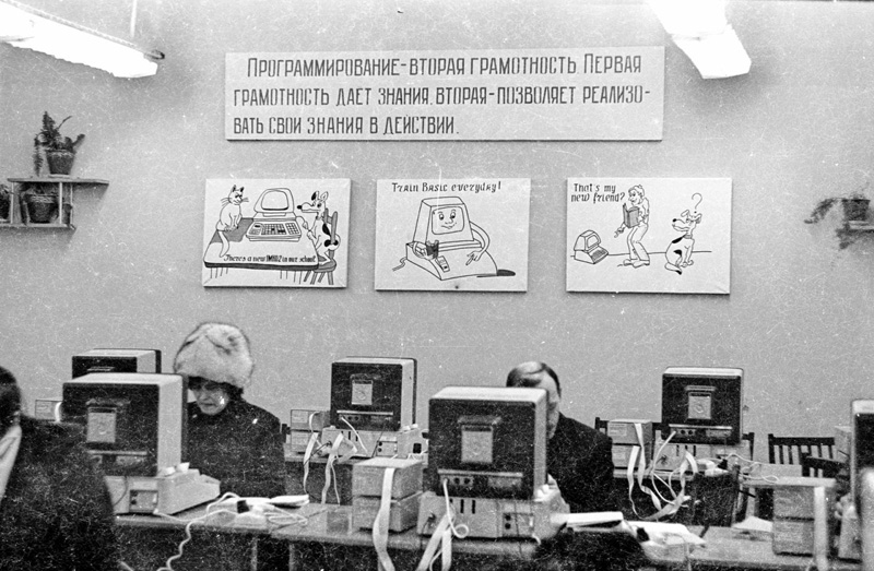 A computer programming classroom in the Soviet Union; a poster on the wall reads 'Train BASIC Everyday!'; 1985