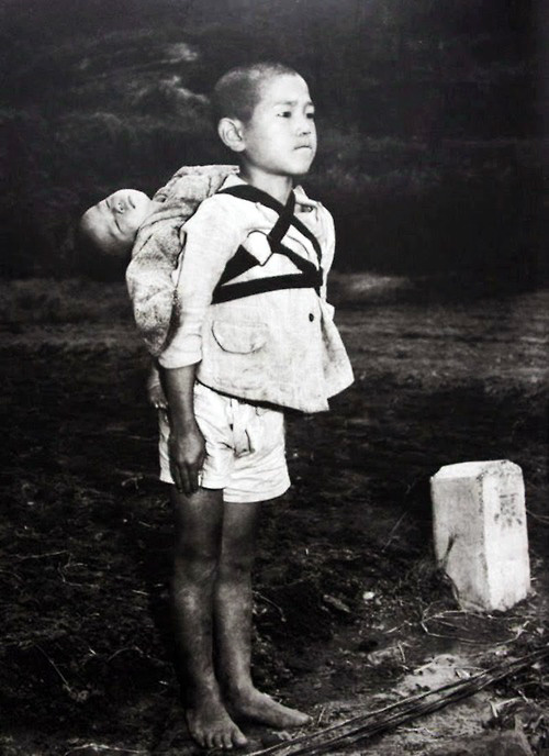 A Japanese boy standing at attention after having brought his dead younger brother to a cremation pyre. Nagasaki, 1945.