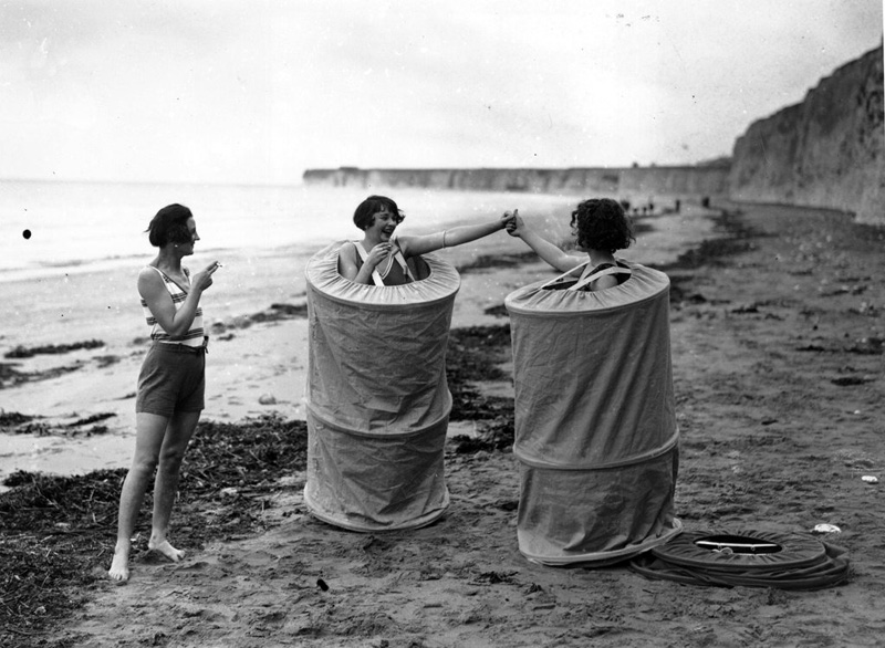 Two women changing discreetly on a beach in 'Skreenette' bathing tents, England, 1929
