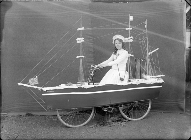 Young woman on a bicycle float of Robert Falcon Scott's boat the 'Terra Nova' by Adam Henry Pearson Maclay, ca. 1910-1913