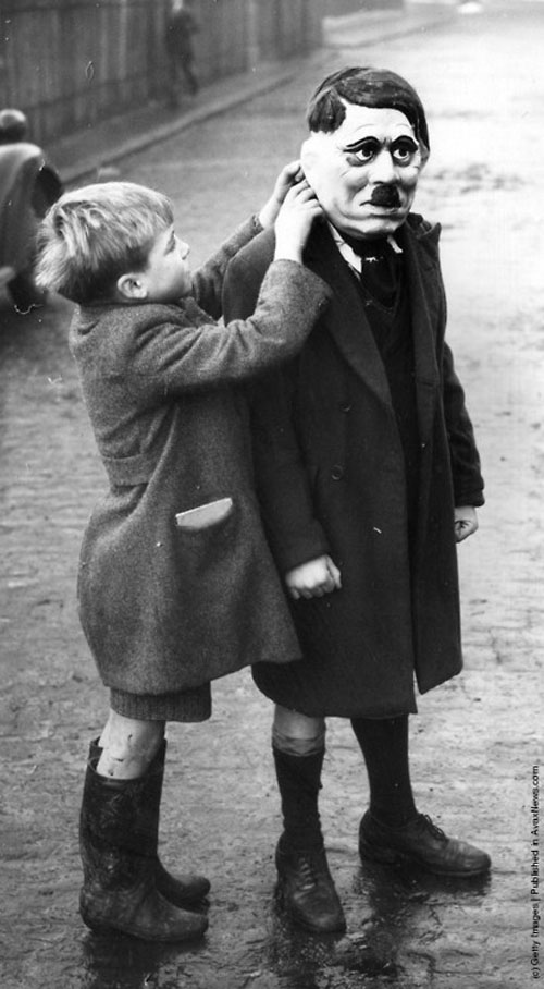 A young boy adjusts his friend's Adolf Hitler mask during a game in King's Cross, London, 1938