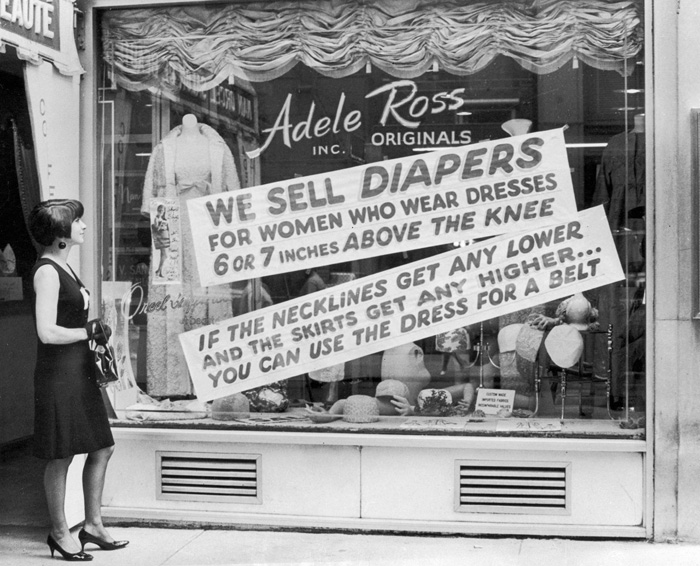 A woman stands outside the Adele Ross clothing design store, looking at an anti-miniskirt sign, New York City, August 1966