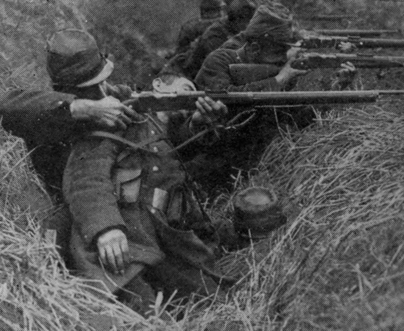 A French soldier fires over the body of a dead comrade.  August, 1914.