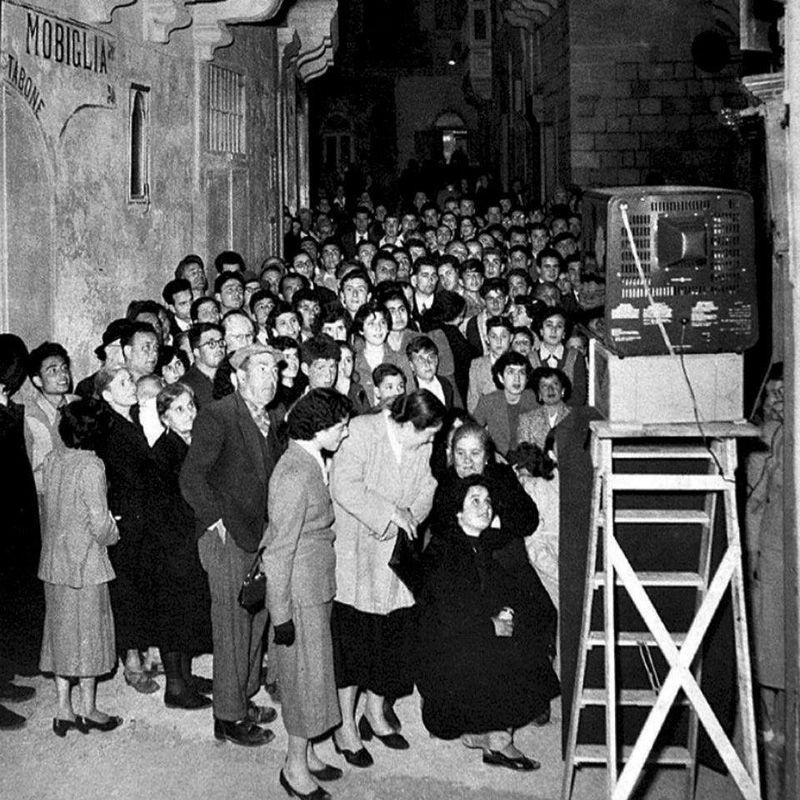 People congregate to watch the first television in Gozo, Sister Island of Malta, 1958