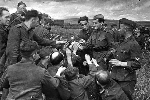 Советский солдат делится сигаретами с немецкими военнопленными. Вторая мировая, 1943 год.