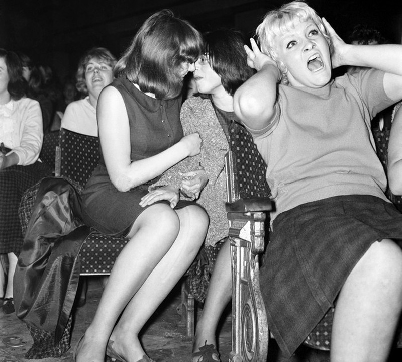 Two girls share a moment at a Beatles concert