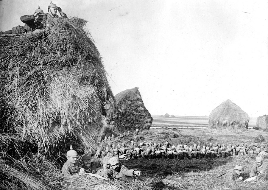 German soldiers make observations from atop, beneath, and behind large haystacks in southwest Belgium1915
