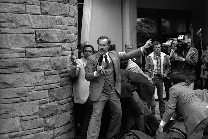 A Secret Service agent brandishes a submachine gun while other agents and police subdue gunman John Hinckley, Jr behind him.