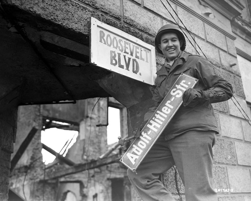 An American soldier replaces Adolf-Hitler-Str. sign with a Roosevelt Blvd one in Berlin, Germany, 1945