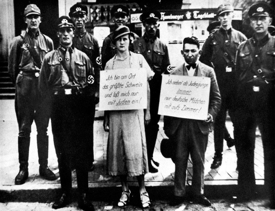 Surrounded by SA Stormtroopers, the woman's sign reads, I am the greatest swine and only get myself mixed up with Jews! and the man's, I am a Jew, I only take German girls to my room! Germany 1935.
