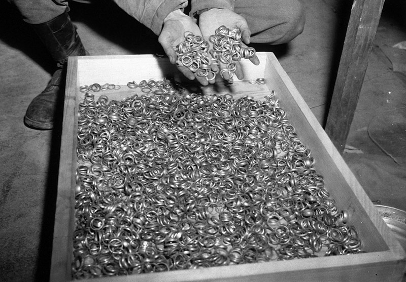 A US soldier inspects thousands of gold wedding bands taken from Jews by the Germans and stashed in the Heilbronn Salt Mines, on May 3, 1945
