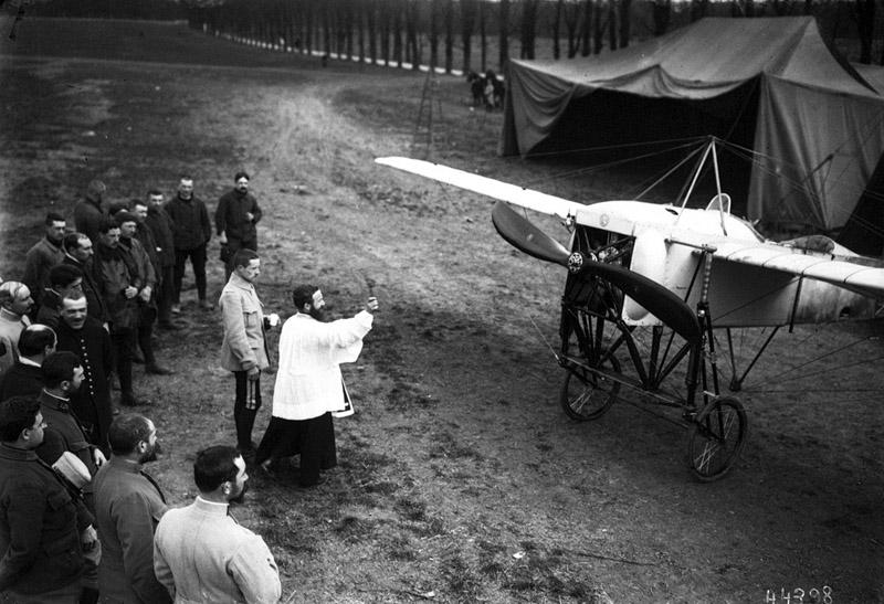 French soldiers gather around a priest as he blesses an aircraft on the Western Front, 1915