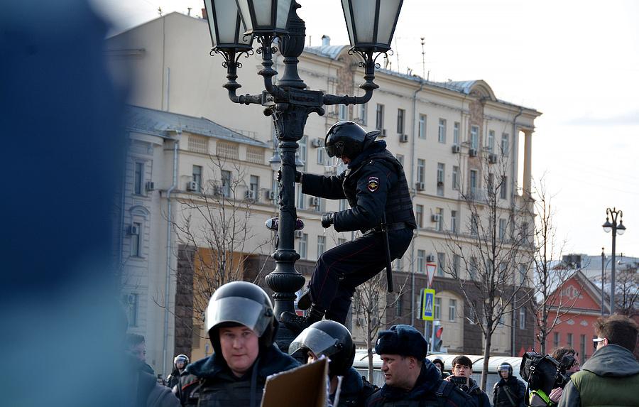 Полицейский снимает кеды с фонаря