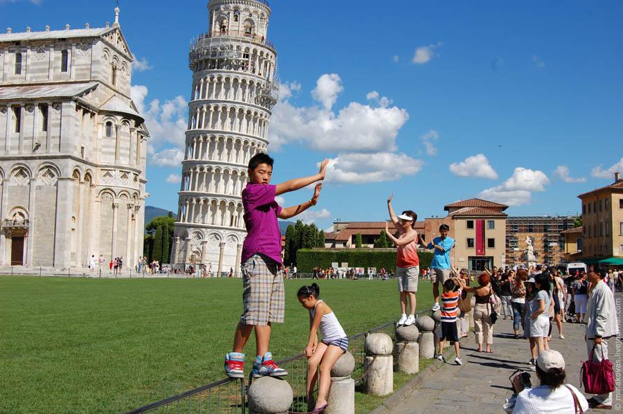 туристы держат пизанскую башню
