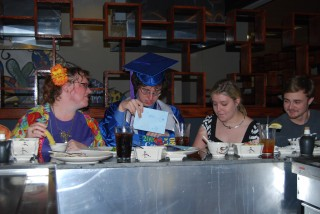 a picture of Critter in his cap and gown, at dinner after Graduation