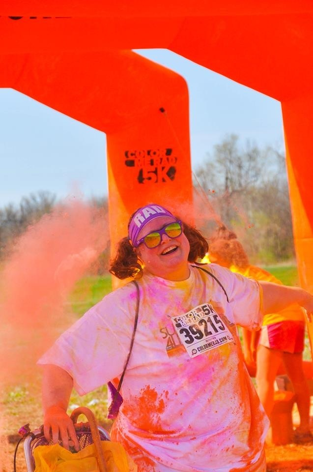 Picture of me going through the Orange Arch in the latest Color Me Rad 5K.  I'm already covered with pink and yellow constarch, and there's a pouf of orange cornstarch in the air around me.  My right hand is resting on the handle for my knee walker and my cane is visible, hanging from my purple basket on my walker.
