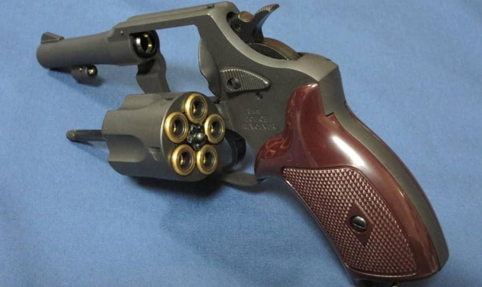 Изображение крупного плана револьвера с открытым барабаном.