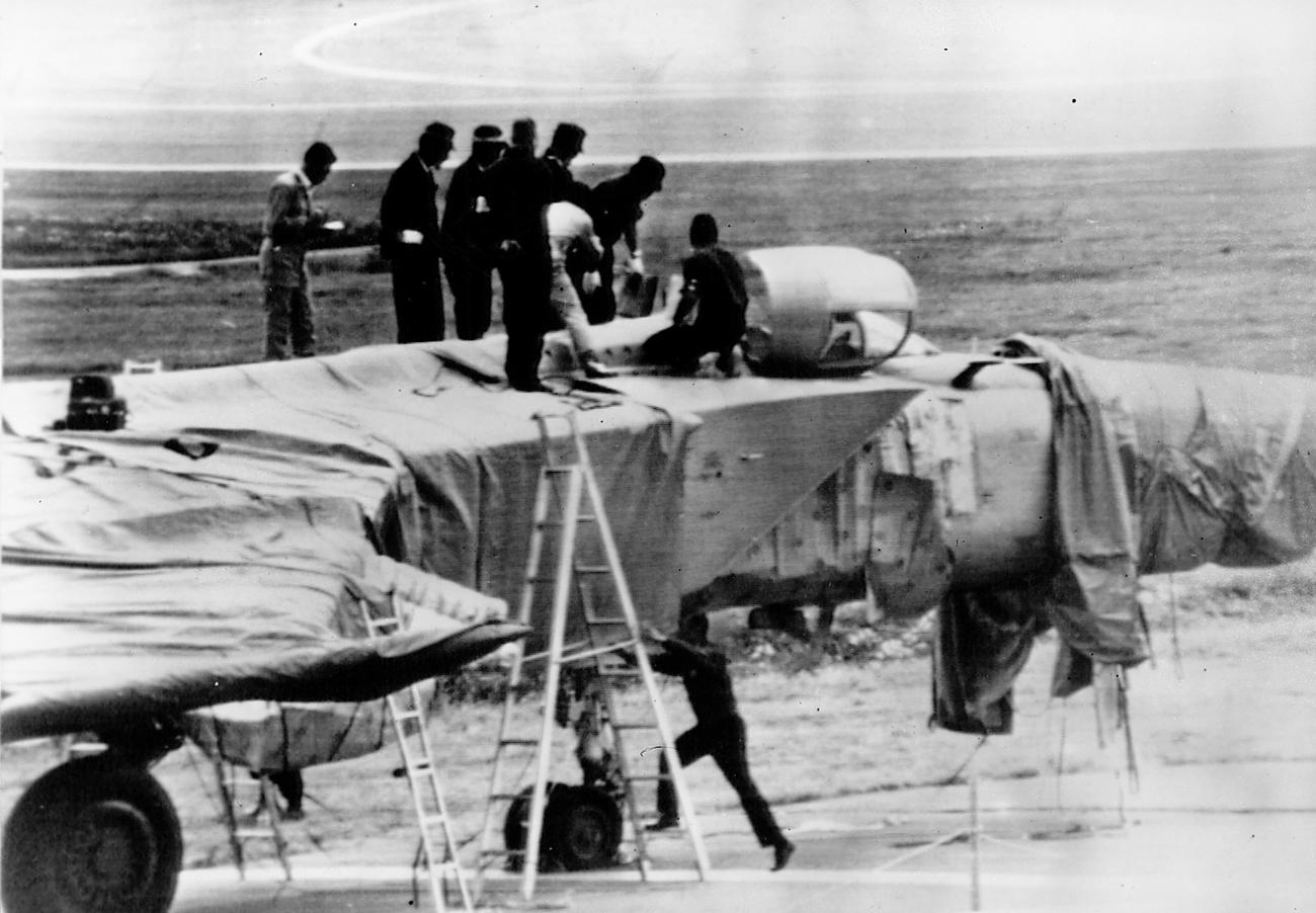 Японцы закрывают самолет брезентом.