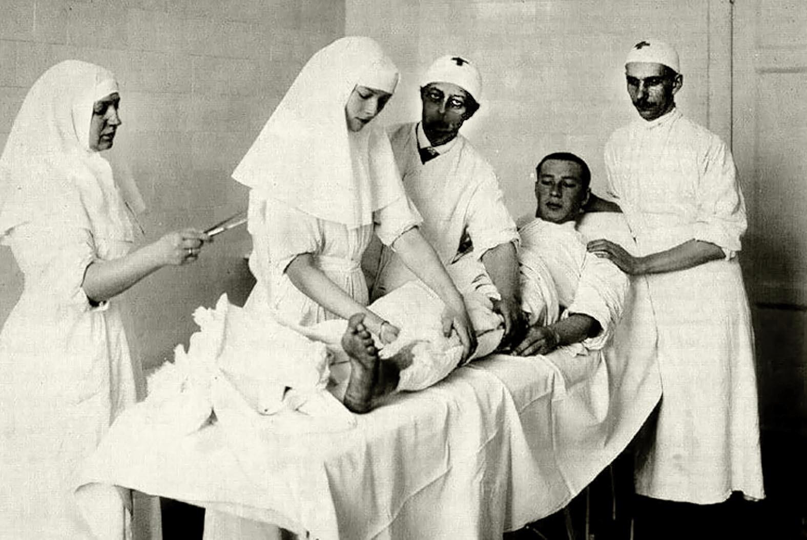 Татьяна делает перевязку корнету Дмитрию Малама. Рядом с Татьяной стоит княжна Вера Гедройц