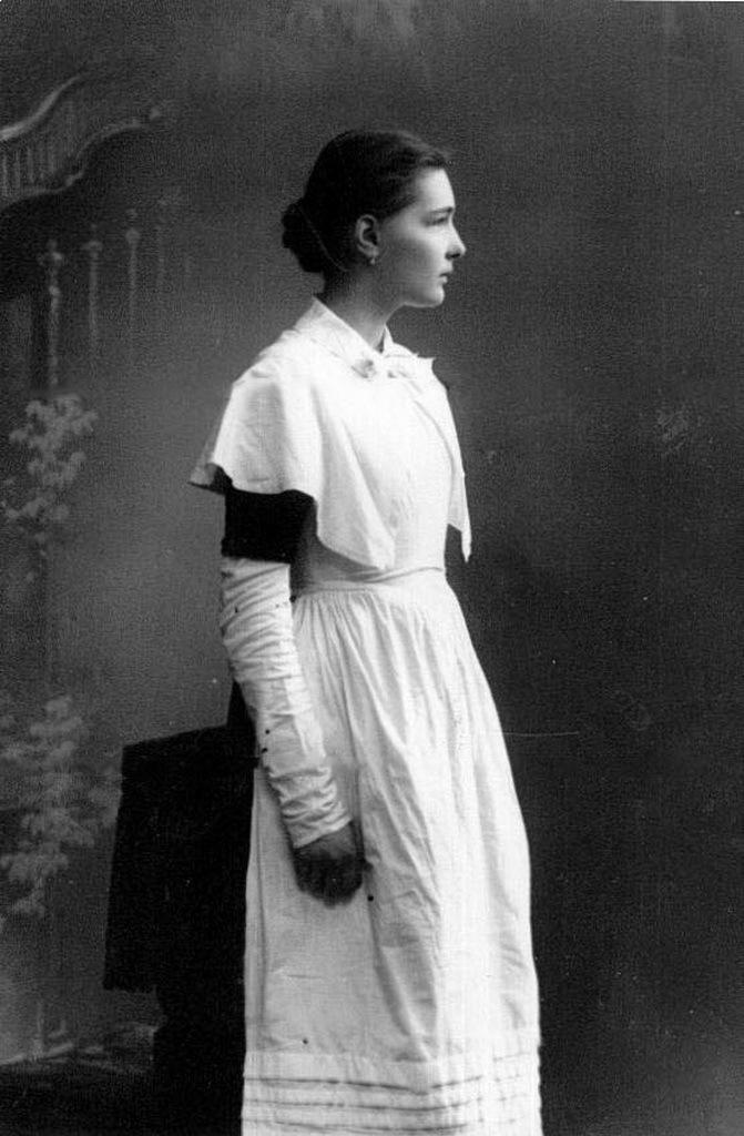 Воспитанница одного из институтов. На снимке хорошо видны все части форменного платья - само платье, белые рукавчики, пелеринка и фартук.