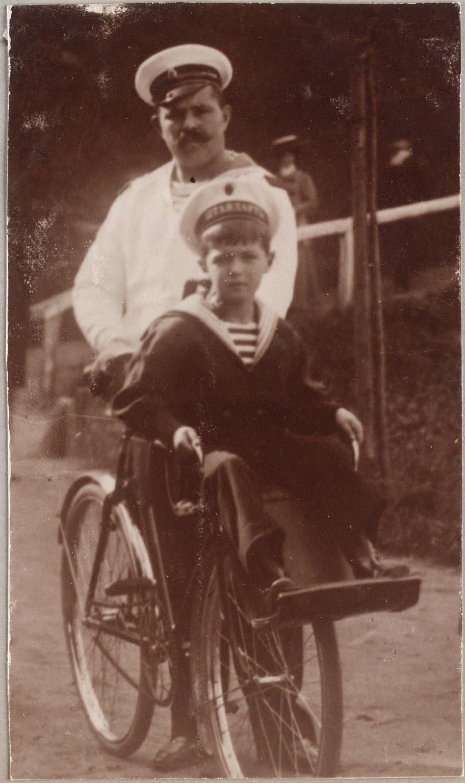 Андрей Деревенько катает Алексея на велосипеде.
