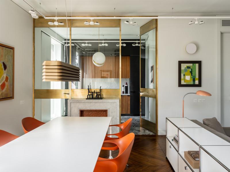 Столовую и кухню разделяет стеклянная перегородка в латунной раме с фальшкамином, задуманным как продолжение оси кухонного стола.. Кухня изготовлена на заказ по эскизам архитекторов Blockstudio.