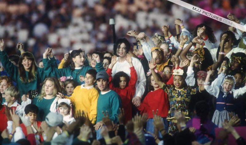 Эми в красном свитере и с розовым бантом, на Суперкубке с Майклом. Ее брат Дэвид в желтом свитере.