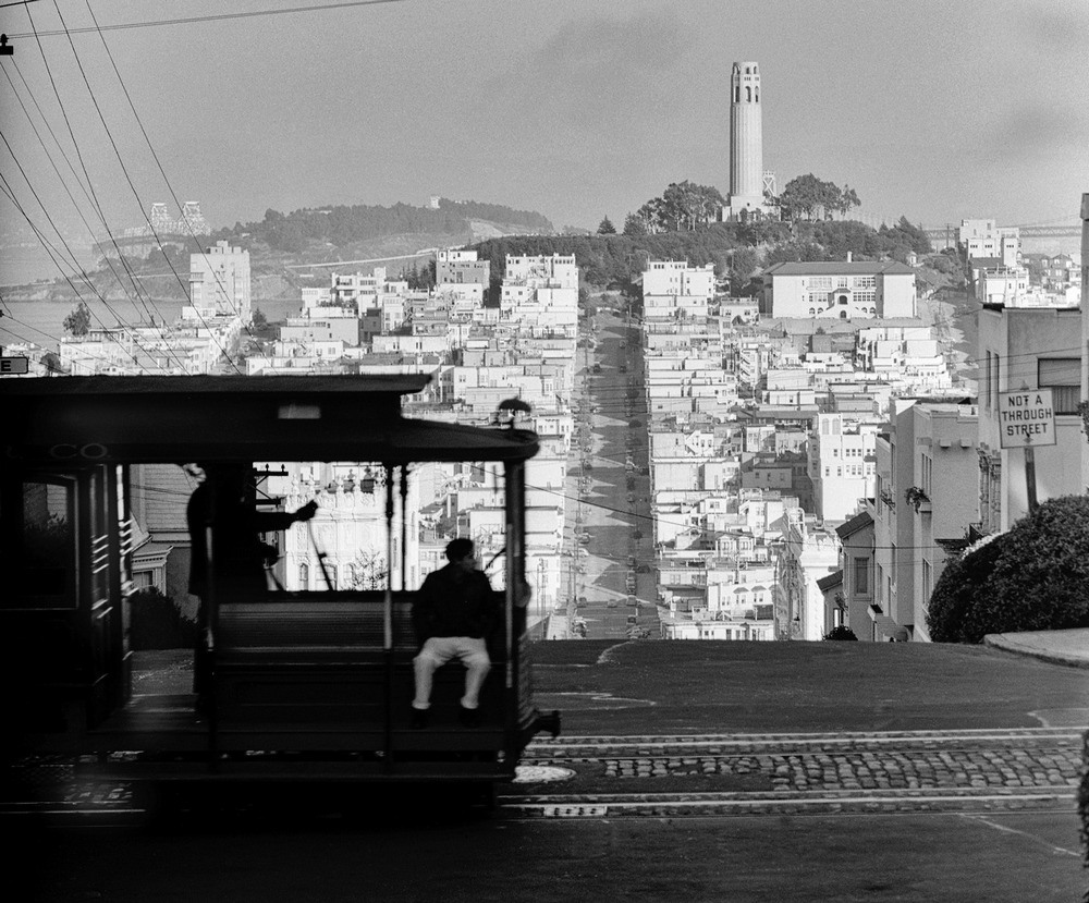 San-Francisco-cable-car-with-Coit-Tower-and-Telegraph-Hill-in-the-distance