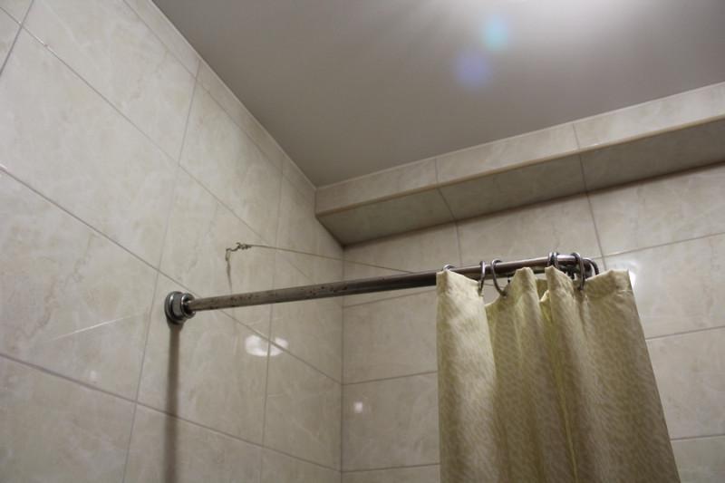 крючок держит палку в ванной
