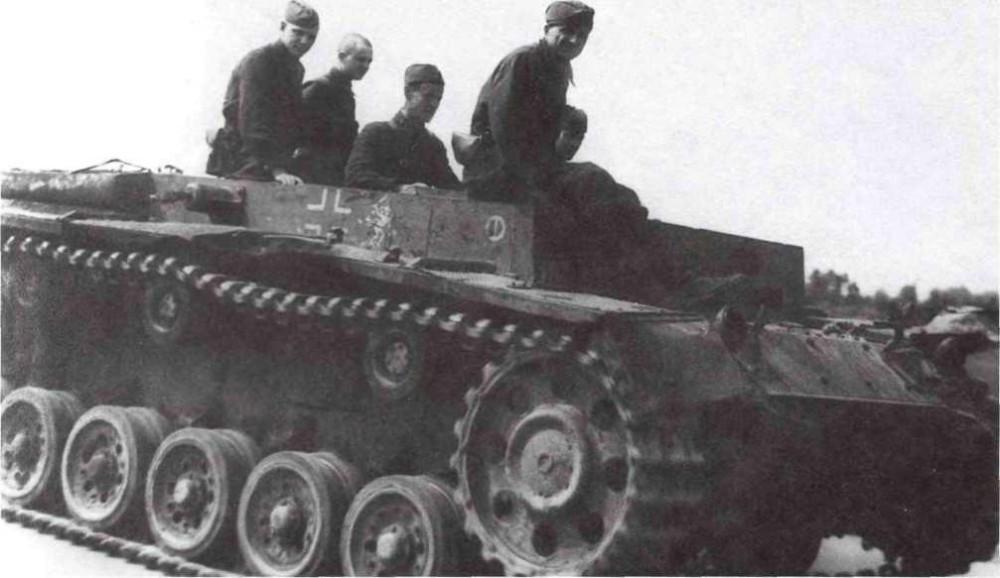 Трофейный танк Pz. III (без башни), захваченный в районе города Н., своим ходом отправляется в мастерские для ремонта, Западный фронт, 1942 год. На борту видна эмблема 11-й немецкой танковой дивизии (РГАКФД)