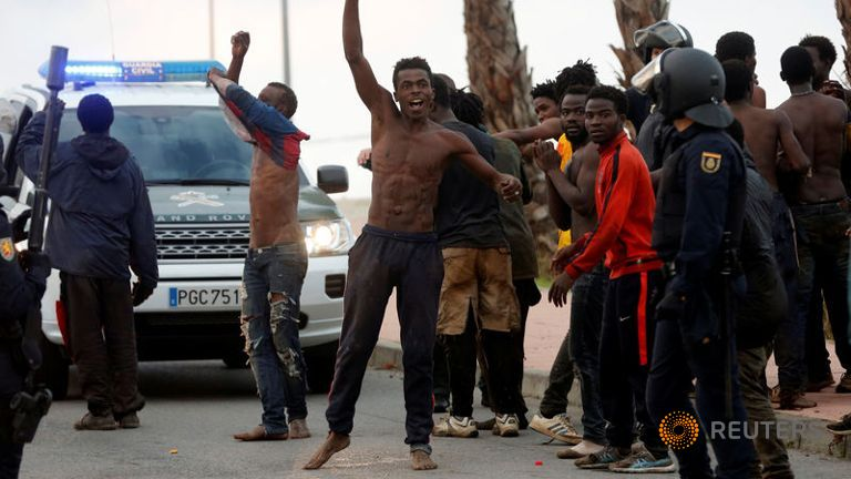 an-african-migrant-celebrates-after-crossing-a-border-fence