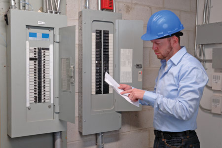 Electrical Inspector with a checklist near circuit breaker panel