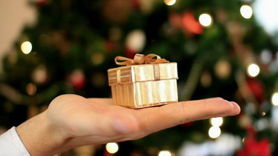 stock-footage-hand-holds-a-gift-in-small-box-christmas-tree-in-background