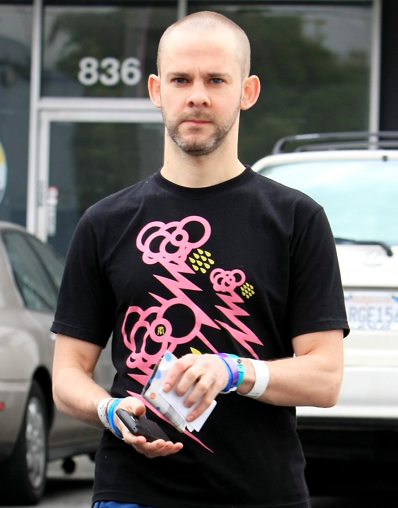 Dom with bald head, black t-shirt with pink scribbles, and blue trackpants.